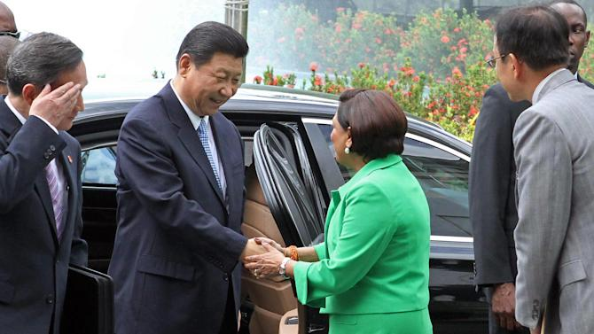 China's President Xi Jinping, center left, is welcomed by Trinidad & Tobago's Prime Minister Kamla Persad-Bissessar to the Diplomatic Center in St. Ann's, Trinidad, Saturday, June 1, 2013. Xi announced China was awarding Trinidad a $250 million loan to build a children's hospital during the first stop of his four-country regional tour in the Americas. He's also traveling to Mexico, Costa Rica and the U.S. (AP Photo/Anthony Harris)