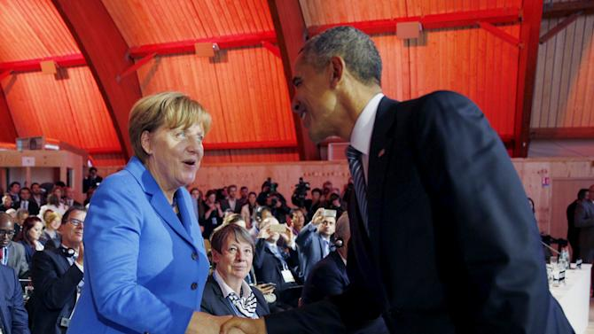 U.S. President Barack Obama greets German Chancellor Angela Merkel during the COP21 climate change summit in Paris, France