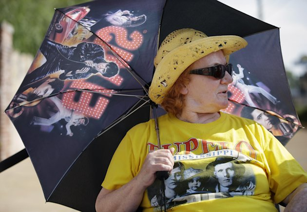 Elvis Presley fan Ann Lawlor, of Croydon, England, waits in line outside Graceland, Presley&#39;s Memphis, Tenn. home, on Wednesday, Aug. 15, 2012. Fans are lined up to take part in the annual candlelight vigil marking the 35th anniversary of Presley&#39;s death. (AP Photo/Mark Humphrey)
