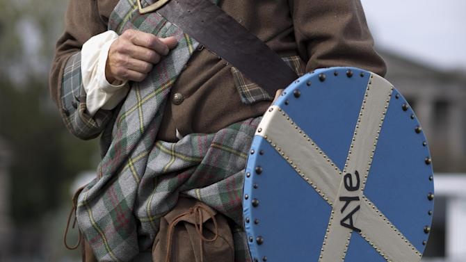 The historical kilt and outfit of Scottish independence referendum Yes campaign supporter and member of a Scottish historical re-enactment group Ed Hastings  are seen as he chats to people on Calton Hill, in Edinburgh, Scotland, Tuesday, Sept. 16, 2014.  The two sides in Scotland's independence debate scrambled Tuesday to convert undecided voters, with just two days to go until a referendum on separation.  The pitch of the debate has grown increasingly urgent. Anti-independence campaigners argue that separation could send the economy into a tailspin, while the Yes side accuses its foes of scaremongering.  (AP Photo/Matt Dunham)