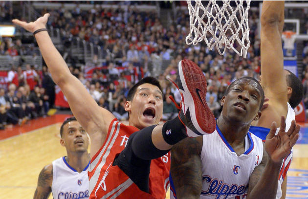 Houston Rockets guard Jeremy Lin, center, falls after putting up a shot as Los Angeles Clippers guard Eric Bledsoe, right, defends and forward Matt Barnes watches during the first half of their NBA ba