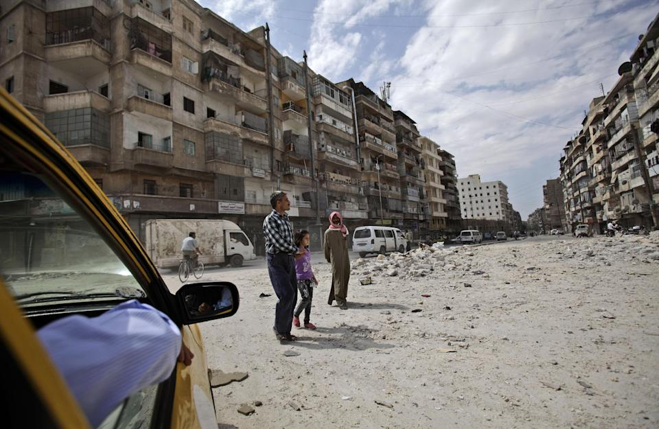 Syrians cross a street next to apartments, many of which have been abandoned due to government shelling, in Aleppo, Syria, Tuesday, Sept. 11, 2012. (AP Photo/Muhammed Muheisen)