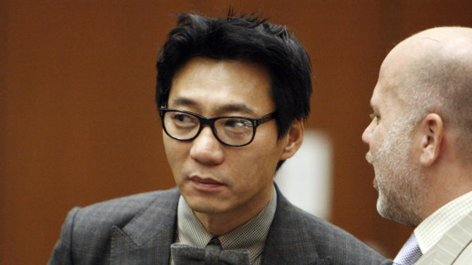 FILE-This Jan. 30, 2012 file photo shows Young Lee, one of the former founders of the Pinkberry yogurt chain stands with his attorney Philip Kent Cohen, right, during his arraignment in the Los Angeles Criminal Courts Building in Los Angeles. Lee has been convicted, Friday, Nov. 8, 2013, of assault with a deadly weapon for striking a transient with a tire iron. Lee was sentenced Friday March 14, 2014, to seven years in prison for beating a homeless man with a tire iron in Los Angeles. (AP Photo/Los Angeles Times, Al Seib, Pool,File)