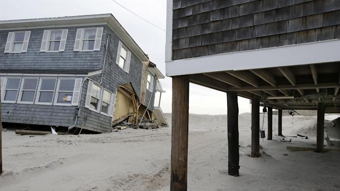 A raised home with modest damage is seen next to a severely damaged beach front home in Mantoloking, N.J., Friday, Feb. 22, 2013. One of the hardest-hit Jersey shore communities, Mantoloking, will allow its residents to begin moving back home Friday. It is the last shore town to do so. It's not a mad rush. The winter population of the barrier island community totals only about 100 and many homes are not yet livable. (AP Photo/Mel Evans)