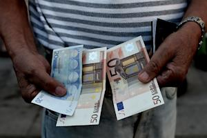 A Greek pensioner holds 120 euros outside a national …
