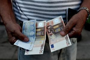 A Greek pensioner holds 120 euros outside a national…