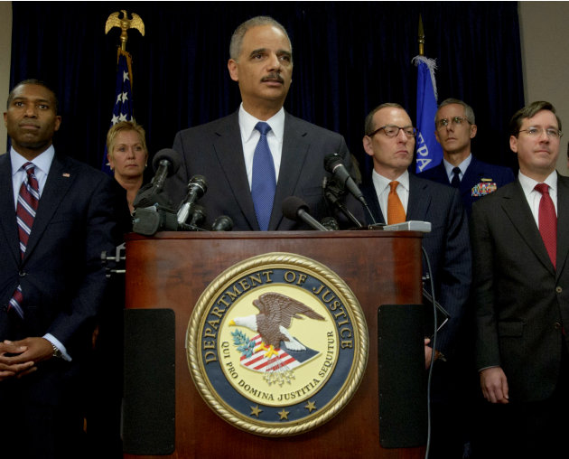 U.S. Attorney General Eric Holder, center, arrives at a press conference followed by Acting Associate Attorney General Tony West, far left, and lead by Assistant Attorney General for the Criminal Divi
