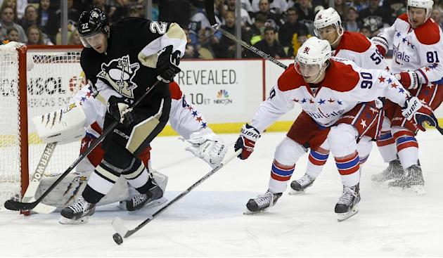 Washington Capitals' Marcus Johansson (90), of Sweden, clears the puck away from Pittsburgh Penguins' Lee Stempniak (22) during the second period of an NHL hockey game, Tuesday, March 11, 2014