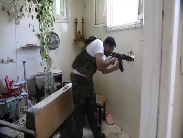 In this image made from video and accessed Saturday, Sept. 1, 2012, a Free Syrian Army fighter fires his weapon at a Syrian Army position through a hole in an empty and destroyed home during fighting