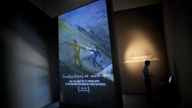 A visitor is seen at a new exhibition dedicated to those who saved Jews during WWII at the Yad Vashem Holocaust memorial in Jerusalem, Wednesday, June 26, 2013. In the spring of 1943, a Polish-Catholic family came upon a naked, Jewish infant in a dark, cold cellar. The child, not even two years old, could neither walk nor talk. Her Jewish parents had been murdered and the family they paid to protect her had abandoned her. (AP Photo/Sebastian Scheiner)