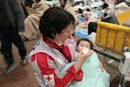 In this photo released by Japanese Red Cross Society, a baby survivor is fed milk by a member of Japanese RC's National Disaster Response Team at the Ishinomaki Red Cross Hospital in Ishinomaki in Miyagi Prefecture (state), Saturday, March 12, 2011, one day after the catastrophic earthquake and tsunami hit northeastern Japan.