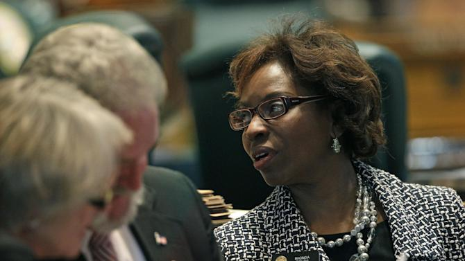 Colorado State Representative Rhonda Fields, speaks to a colleague during a debate period for a gun control bill which she sponsored, inside the Colorado State Legislature, in Denver, Friday March 15, 2013. A landmark expansion of background checks on firearm purchases was approved Friday by lawmakers in Colorado, a politically moderate state that was the site of last year's gruesome mass shooting at a suburban Denver movie theater. (AP Photo/Brennan Linsley)