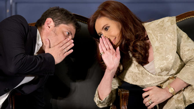 Argentine President Cristina Fernandez, right, speaks with Economy Minister Axel Kicillof during the ceremony for the 160th anniversary of the Buenos Aires Stock Exchange in Buenos Aires, Argentina, Wednesday, Aug. 20, 2014. Argentina's government is proposing to change the way it pays holders of the country's debt, shifting it out of the U.S. financial and legal systems as a way to end the default triggered by a legal battle with U.S. investors. (AP Photo/Victor R. Caivano)