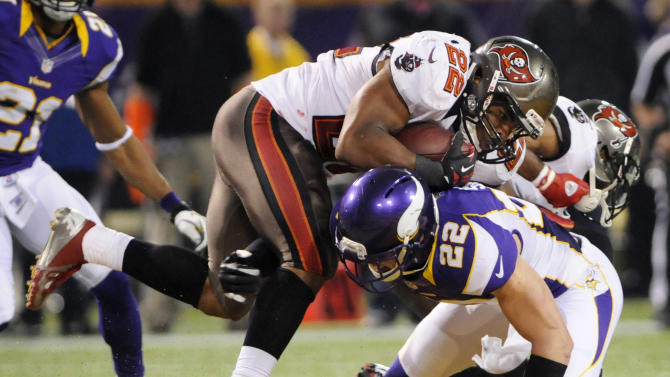 Tampa Bay Buccaneers running back Doug Martin, left, runs over Minnesota Vikings free safety Harrison Smith during the second half of an NFL football game Thursday, Oct. 25, 2012, in Minneapolis. (AP Photo/Jim Mone)