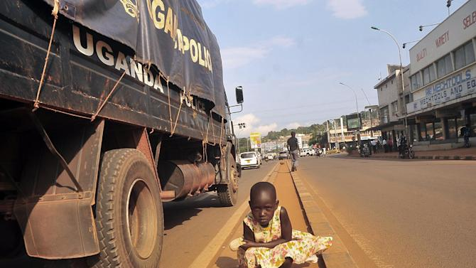 """A Ugandan street child poses in the middle of the streets as a police truck goes past her, in Kampala, Uganda, Thursday,July 17, 2014. Homeless children in Uganda's urban centers face beatings and abuse at the hands of police and local officials, Human Rights Watch charged in a new report that urges Ugandan authorities to protect street children from targeted roundups and arbitrary detentions. A police spokesman said the allegations are """"totally not true."""" (AP Photo / Stephen Wandera)"""