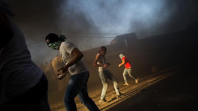 """FILE - In this Tuesday, Sept. 18, 2012 file photo, masked Palestinians throw stones towards Israeli security forces, not pictured, during clashes that erupted after a demonstration against an anti-Islam film called """"Innocence of Muslims"""" that ridicules Islam's Prophet Muhammad, in Shuafat refugee camp, Jerusalem. U.S.-funded ads on Pakistani television include President Barack Obama extolling America's religious tolerance. To many in the Muslim world, this misses the mark in efforts to calm the outrage over a film mocking the Prophet Muhammad. (AP Photo/Bernat Armangue, File)"""