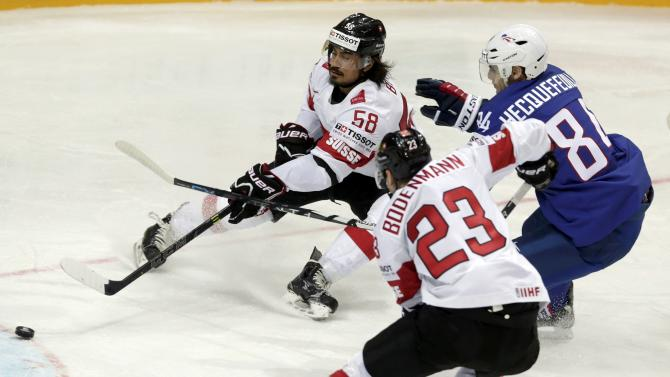 France's Hecquefeuille fights for the puck with Switzerland's Blum and Bodenmann during their Ice Hockey World Championship game at the O2 arena in Prague