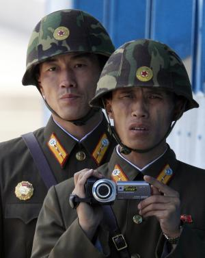 North Korean soldiers film south side at the border village of the Panmunjom (DMZ) that separates the two Koreas since the Korean War, in Paju, north of Seoul, South Korea, Sunday, April 24, 2011.  (AP Photo/Lee Jin-man, Pool)