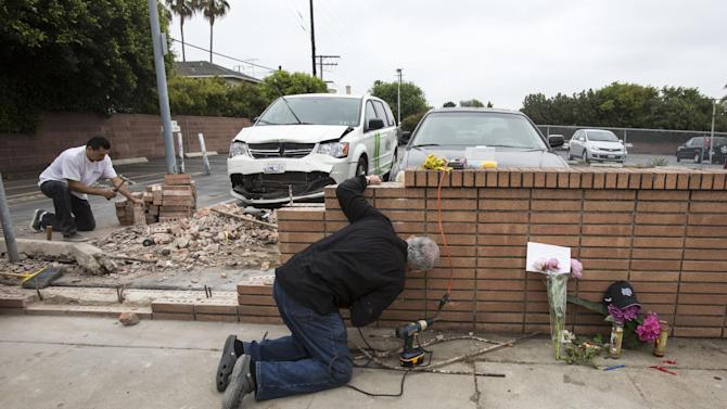 Akiva Sherman, right, 62,  repairs the wall  next to a makeshift memorial Sunday, June 9, 2013, where a victim's vehicle crashed during the shootings at Santa Monica College in Santa Monica, Calif. The shootings on Friday left six people dead, including the gunman.   (AP Photo/Ringo H.W. Chiu)