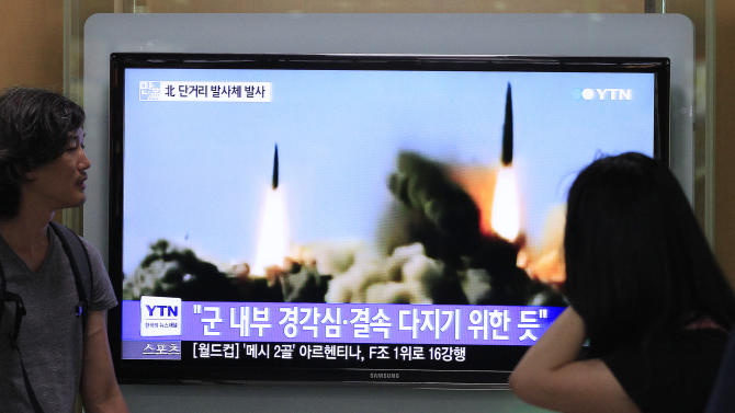 """People watch a TV news program showing the missile launch conducted by North Korea, at Seoul Railway Station in Seoul, South Korea, Thursday, June 26, 2014. North Korea fired three short-range projectiles Thursday into the waters off its east coast, a South Korean defense official said. The move was most likely a routine test-firing, but the official said it could also be meant to stoke tensions with Seoul. The writing on the screen reads """"The missiles were launched to alert and express its internal solidarity."""" (AP Photo/Ahn Young-joon)"""