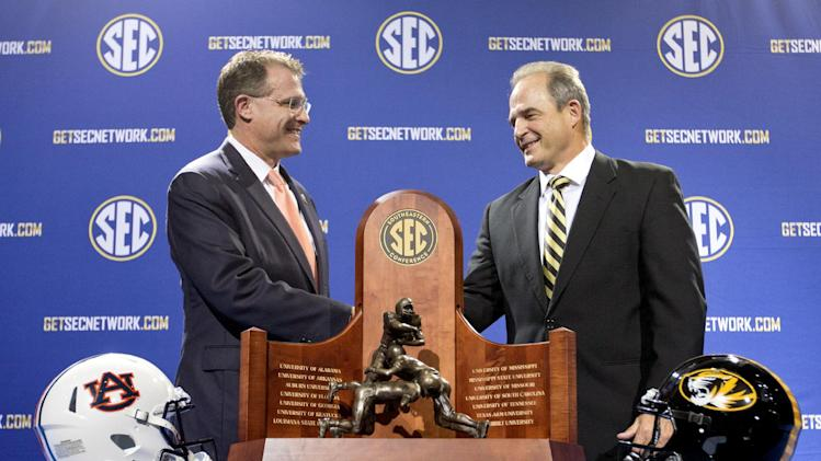 Auburn head coach Gus Malzahn, left, shakes hands with Missouri head coach Gary Pinkel during a photo op at a press conference ahead of Saturday's Southeastern Conference championship football game, Friday, Dec. 6, 2013, in Atlanta