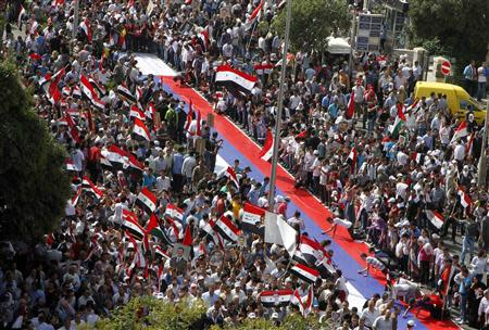 Supporters of Syrian President Bashar al-Assad's sign a large Russian flag during a rally at al-Sabaa Bahrat square in Damascus