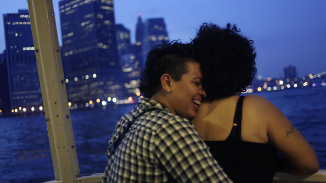 Nirvana Galvez, left, hugs her newlywed Ruth Galvez on a cruise hosted by Marriage Equality New York in New York, Sunday, July 24, 2011, as they pass by lower Manhattan. The couple are domestic partners where they live in California, but flew to New York to get married on the first day it became legal in the state. New York became the sixth and largest state to recognize same-sex weddings in a close state Senate vote on June 24 after strong lobbying by Cuomo and advocates. The first gay marriages in New York were performed just after midnight and continued through the day at municipal offices that opened for special weekend hours. (AP Photo/Seth Wenig)