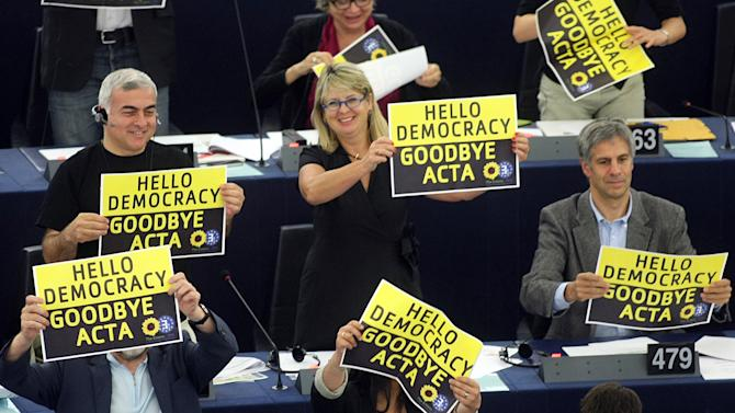 """Green Party members of the European parliament demonstrate against the ACTA project (Anti-Counterfeiting Trade Agreement) during the vote Wednesday, July 4, 2012 at the European Parliament in Strasbourg, eastern France. The European Parliament has overwhelmingly defeated the international ACTA anti-piracy agreement, after fears that it would limit Internet freedom. A """"no"""" vote in the Parliament on Wednesday would kill the treaty as far as the European Union is concerned. Supporters say that ACTA — the Anti-Counterfeiting Trade Agreement — is needed to harmonize international standards to protect the rights of those who produce music, movies, pharmaceuticals, fashion goods and other products that often fall victim to piracy and intellectual property theft. Opponents say it would stifle free access to information. (AP Photo/Christian Lutz)"""