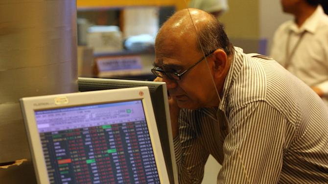 An investor looks at stock prices at a bank in Kuala Lumpur, Malaysia, Monday, Aug. 8, 2011. Asian stocks nose-dived Monday as the first-ever downgrade of the U.S. government's credit rating jolted the global financial system, reinforcing fears of a rapid slowdown in economic growth. (AP Photo/Lai Seng Sin)