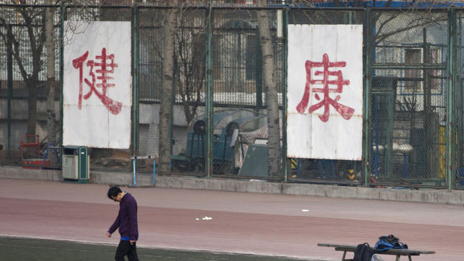 """In this Saturday, Jan. 19, 2013 photo. a college student kicks a soccer ball in front of Chinese characters on the fence reading """"good health"""" in Beijing. Despite its formidable performance in recent Olympic Games, China has found itself in a crisis of declining fitness among its youngsters. (AP Photo/Alexander F. Yuan)"""