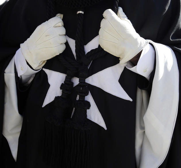 A members of the Knights of Malta wears a dark cloak with a white, eight-pointed Maltese Cross on the front during a procession towards St. Peter's Basilica for a celebration to mark the 900th anniver