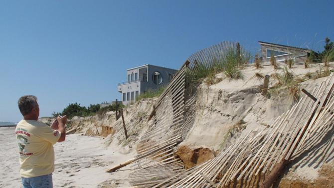 Robert Giovannetti, a construction specialist with the New Jersey Department of Environmental Protection, inspects badly eroded dunes in the Holgate section of Long Beach Township, N.J.Monday Aug. 29, 2011. (AP Photo/Wayne Parry)