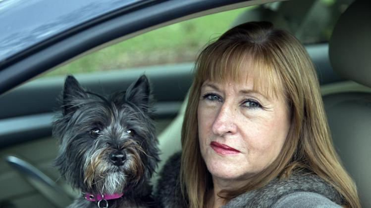 "In this photo taken Nov. 2, 2012, Diane Spitaliere and her pet dog Izzie sit in her car outside her house in Alexandria. Baby boomers, that giant population bubble born between 1946 and 1964, started driving at a young age and became more mobile than any generation before or since. Spitaliere, a 58-year-old who recently retired after working 38 years at the Federal Aviation Administration, said the idea of moving to a retirement or assisted living community ""is just very unappealing to me.""    (AP Photo/Manuel Balce Ceneta)"