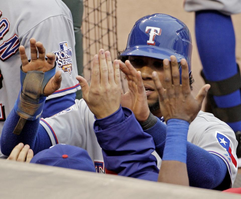 Texas Rangers' Elvis Andrus is congratulated by teammates after scoring on a hit by Vladimir Guerrero during the first inning of Game 1 of baseball's World Series against the San Francisco Giants Wednesday, Oct. 27, 2010, in San Francisco. (AP Photo/Eric Risberg)