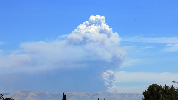 The Powerhouse Fire burning in the Angeles National Forest northwest of Los Angeles sends up a huge plume of smoke on Saturday, June 1, 2013. Smoke from the fire made visibility hazy in the San Fernando Valley, foreground. The blaze has burned thousands of acres of brush since it erupted Thursday afternoon near a utility powerhouse. (AP Photo/John Antczak)