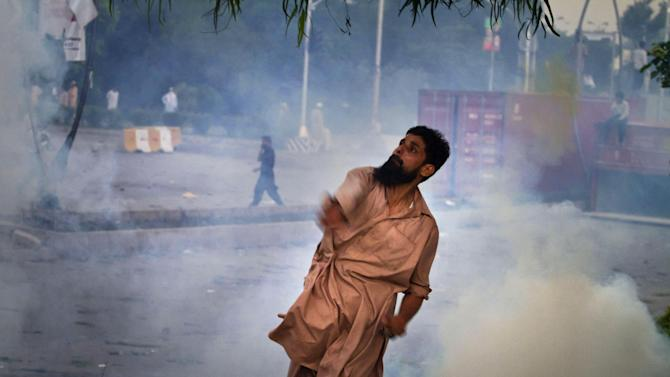 A Pakistani protester hurls back a tear gas canister fired by police, not pictured, during clashes that erupted as protestors tried to approach the U.S. embassy, in Islamabad, Pakistan, Thursday, Sept. 20, 2012. Hundreds of Pakistanis angry at an anti-Islam film that denigrates the religion's prophet clashed with police in the Pakistani capital Thursday, the most violent show of anger in a day that saw smaller demonstrations in Indonesia, Iran and Afghanistan. (AP Photo/Anjum Naveed)