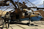 French army deminers secure a MI25 helicopter in a hangar at the Gao airport, on February 9, 2013. Residents of a village near Gao, the largest city in the north, detained two youths they said were wearing explosive-rigged belts on the same road where the suicide bombing on Friday wounded a soldier at a checkpoint