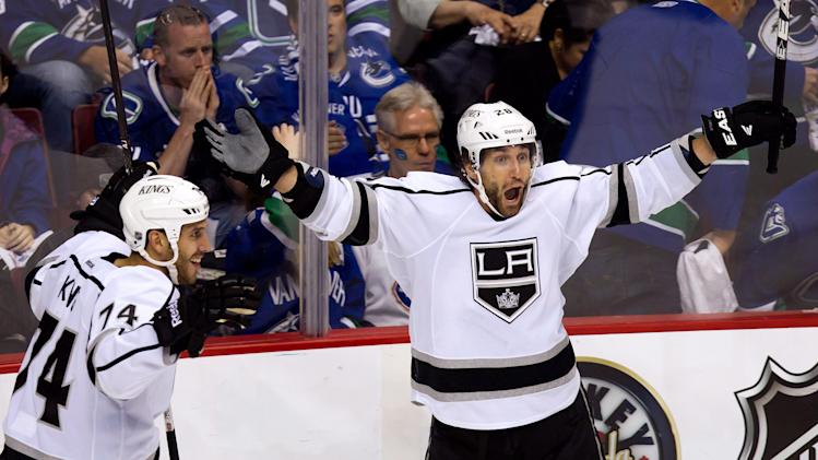 Los Angeles Kings' Jarret Stoll, right, and Dwight King celebrate after Stoll scored the game-winning goal against Vancouver Canucks' goalie Cory Schneider during the first overtime period of game 5 of an NHL Western Conference quarterfinal Stanley Cup playoff hockey series in Vancouver, British Columbia  on Sunday April 22, 2012. Los Angeles won the series 4 games to 1. (AP Photo/The Canadian Press, Darryl Dyck)