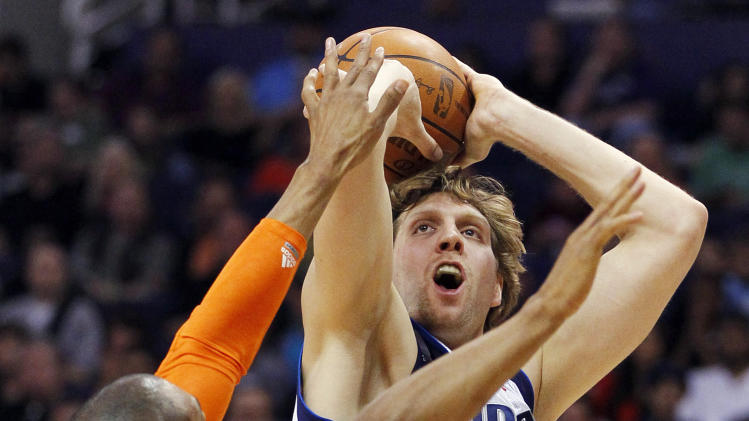 Dallas Mavericks' Dirk Nowitzki, of Germany, right, shoots over Phoenix Suns' Grant Hill during the first half of an NBA basketball game, Thursday, March 8, 2012, in Phoenix. (AP Photo/Matt York)