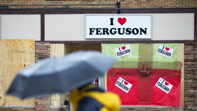 "A pedestrian passes a boarded up storefront selling ""I Love Ferguson"" paraphernalia, Sunday, Nov. 23, 2014, in Ferguson, Mo. Ferguson and the St. Louis region are on edge in anticipation of the announcement by a grand jury whether to criminally charge Officer Darren Wilson in the killing of 18-year-old Michael Brown. (AP Photo/David Goldman)"