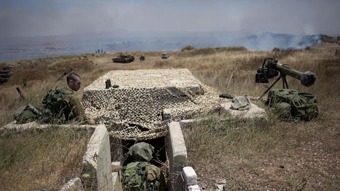 Israeli soldiers sit in a position on the border with Syria on the Israeli controlled Golan Heights as smoke rises following explosions, Tuesday, July 16, 2013. Three mortar shells exploded on the Israeli side of the border fence with Syria on the Golan Heights Tuesday morning. No casualties or damage were reported from the incident, and there are currently no special security instructions for residents of the area. The shells fell at 6 a.m. local time, and the IDF was combing the area to collect any residual material from the exploded ordinance, the IDF Spokesperson's Unit said. According to the IDF, the fire was not directed at Israel, but was fired as part of the battle currently raging in the nearby Syrian village of Al-Madriya, where rebels are clashing with regime forces. (AP Photo/Ariel Schalit)