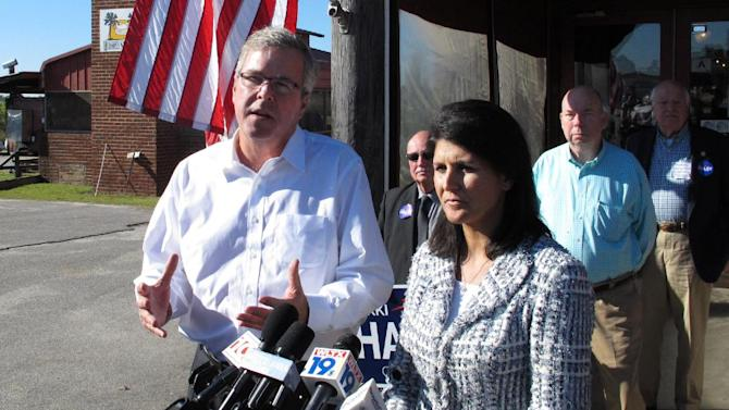 Former Florida Gov. Jeb Bush, left, with South Carolina Gov. Nikki Haley, right, speaks to reporters after a Haley campaign event on Thursday, Oct. 23, 2014, in Lexington, S.C. Haley said she was proud to campaign for he re-election with Bush because she would never be leading South Carolina without Bush's help. (AP Photo/Jeffrey Collins)