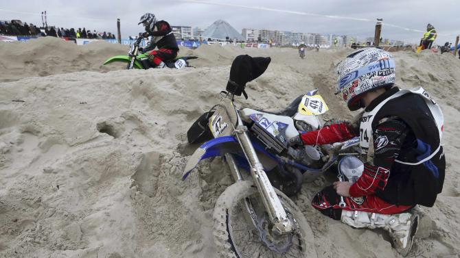 """A biker tries to repair his motorbike as he takes part in the """"Enduropale"""" motorcycle endurance race on the beach of Le Touquet"""