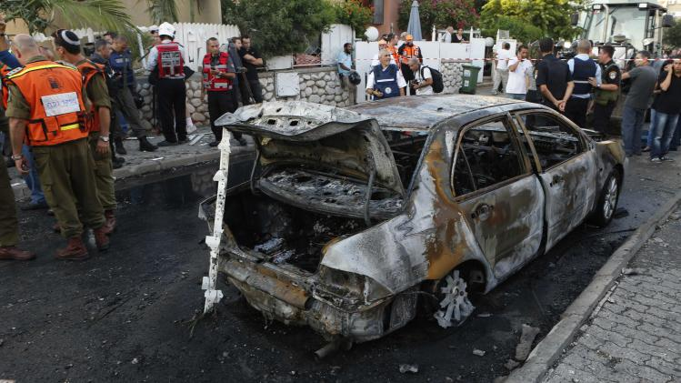 Israeli firefighters, medics and soldiers stand next to a burnt car at the scene after a rocket fired by Palestinian militants landed in Kiryat Gat