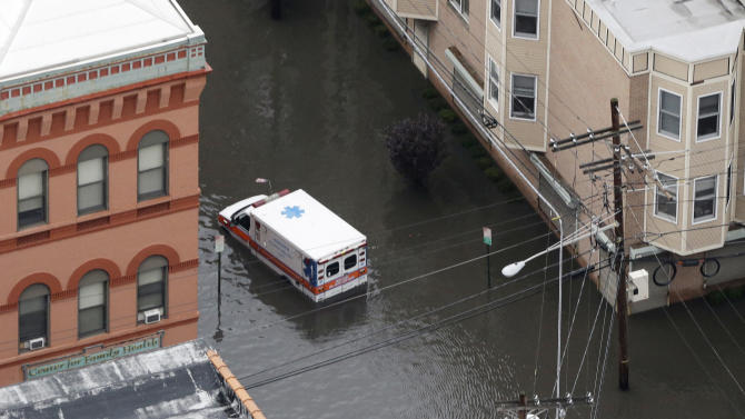 An ambulance is submerged in floodwaters in the wake of superstorm Sandy on Tuesday, Oct. 30, 2012, in Hoboken, N.J. Sandy, the storm that made landfall Monday, caused multiple fatalities, halted mass transit and cut power to more than 6 million homes and businesses. (AP Photo/Mike Groll)