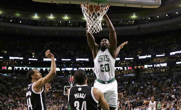 Boston Celtics forward Brandon Bass (30) dunks over Brooklyn Nets forward Paul Pierce (34) during the first quarter of an NBA basketball game, Friday, March 7, 2014, in Boston. The Celtics defeated th