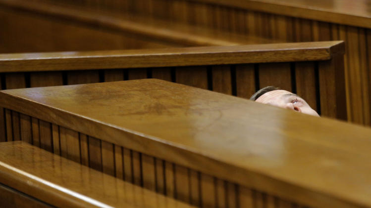 Oscar Pistorius leans back after applying eye drops in court in Pretoria, South Africa, Friday, March 14, 2014. Pistorius is charged with the shooting death of his girlfriend Reeva Steenkamp, on Valentines Day in 2013. (AP Photo/Kim Ludbrook, Pool)
