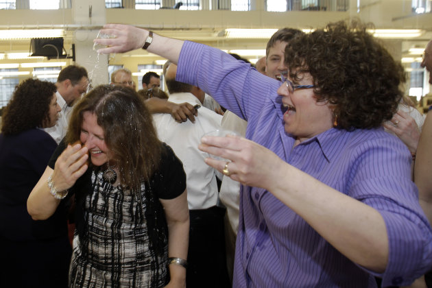 The Philadelphia Inquirer's Susan Snyder, left, has a drink poured on her in celebration by Carolyn Davis after the paper won the Pulitzer Prize for public service, Monday, April 16, 2012, in Philadel