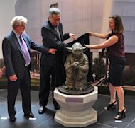 George Lucas (left), Singapore Prime Minister Lee Hsien Loong (centre) and Kathleen Kennedy, president of Lucasfilm, unveil a statue of Yoda at Lucasfilm's new production facility, the Sandcrawler in Singapore on January 16, 2014