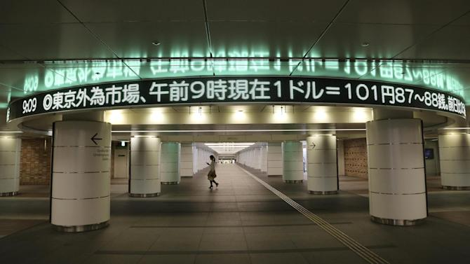 A woman walks under a screen indicating the U.S. dollar rate in Tokyo, Tuesday, June 17, 2014. Japan's benchmark Nikkei 225 rose 0.4 percent to 14,991.04, rebounding from a sharp 1.1 percent drop the day before as the yen weakened 0.1 percent to 101.97 versus the dollar. (AP Photo/Koji Sasahara)